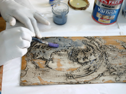 Painting the carborundum/varnish mixture onto the plate surface